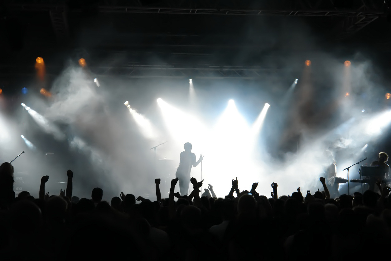 Man on stage with concert crowd below and bright spotlights